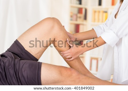 Female physio therapist hands working on male patients legs, holding and bending, blurry clinic background