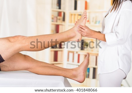 Female physio therapist hands working on male patients lower leg and ankle, blurry clinic background