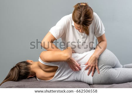 Female physiotherapist doing manipulative spine treatment on young patient.