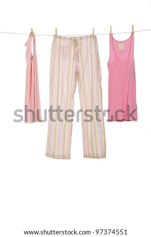 female pink shirt and trousers clothespins on rope - stock photo