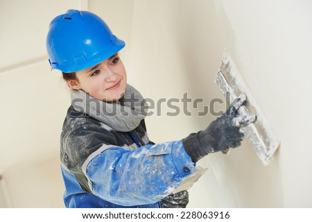 female plasterer painter at indoor wall renovation decoration stopping with spatula and plaster - stock photo