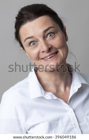 female portrait - gorgeous mature woman smiling with elegance, looking with eyes wide open for fun and joy, grey background - stock photo