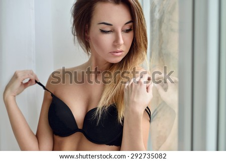 Female portrait of cute lady in black bra indoors. Close-up beautiful sexy model girl in elegant pose. Beauty brunette woman with hairstyle - stock photo