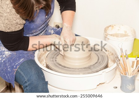 Female Potter creating a earthen jar on a Potter's wheel - stock photo