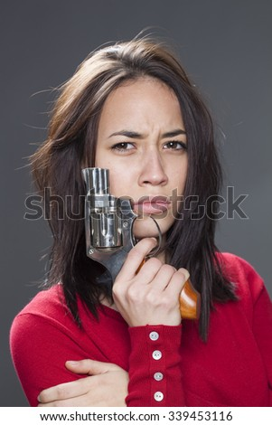 female power concept - frowning attractive multi-ethnic girl showing a gun for revenge or fighting against abuse