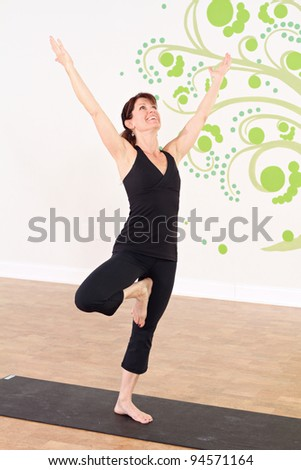 Female practicing yoga in a studio setting - stock photo