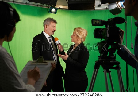 Female Presenter Interviewing  In Television Studio With Crew In Foreground - stock photo