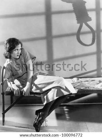 Female prisoner with shadow of noose - stock photo