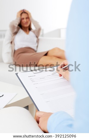 Female psychologist making note while patient talking - stock photo