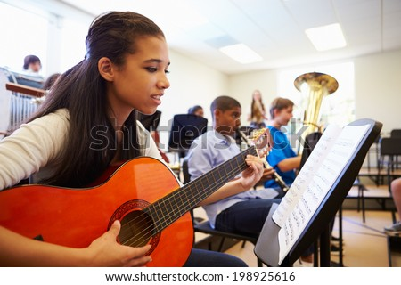 Female Pupil Playing Guitar In High School Orchestra - stock photo