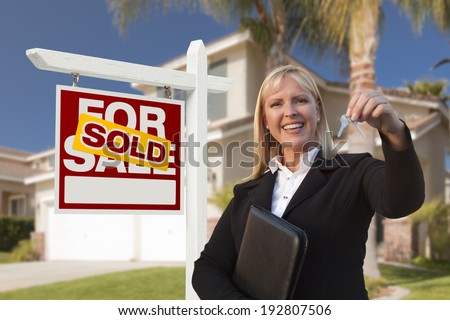 Female Real Estate Agent Handing Over the House Keys in Front of a Beautiful New Home and Real Estate Sign. - stock photo