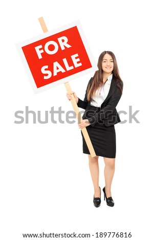 Female real estate agent holding a for sale sign isolated on white background