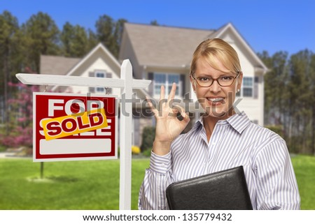 Female Real Estate Agent in Front of Sold Home For Sale Sign and House.