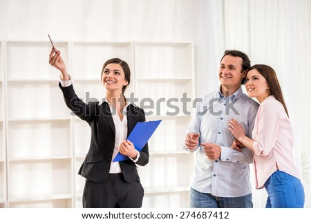 Female realtor is showing a flat to young couple. - stock photo