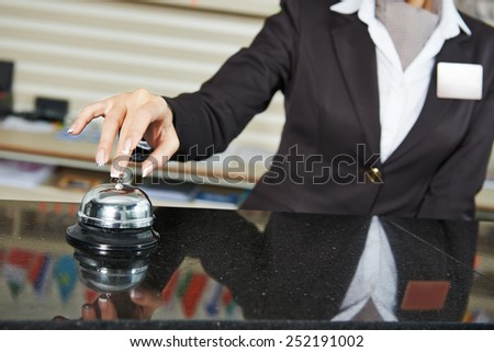 female receptionist worker ringing at hotel counter bell - stock photo