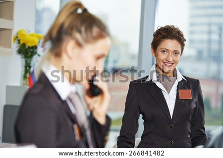 female receptionist workers standing at hotel counter - stock photo