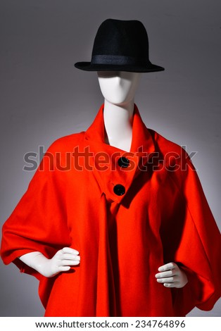 female red clothing with hat on mannequin on gray background - stock photo