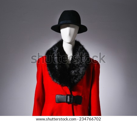 female red fur clothing with black hat on mannequin on gray background - stock photo