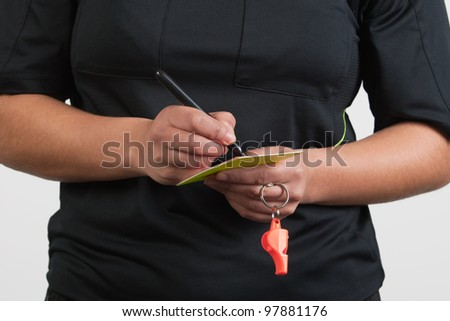 female referee writing on the card - stock photo