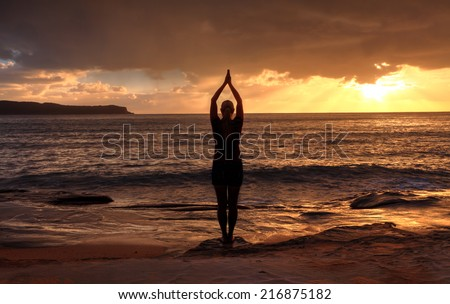 Female relaxing at sunrise, performing tadasana - mountain pose by the sea at sunrise - stock photo