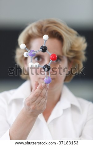 Female researcher analyzing a molecular model in a laboratory. - stock photo