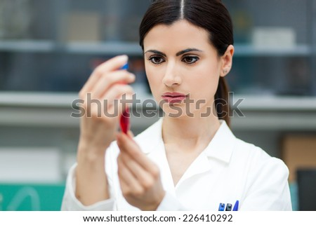 Female researcher analyzing a test tube - stock photo
