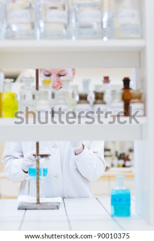 female researcher/chemistry student carrying out research in a chemistry lab (color toned image; shallow DOF)
