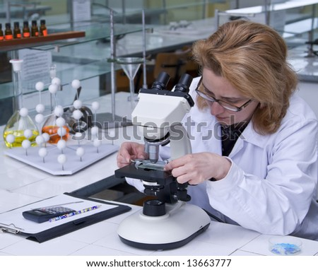 Female researcher fixing a spangle on a microscope.