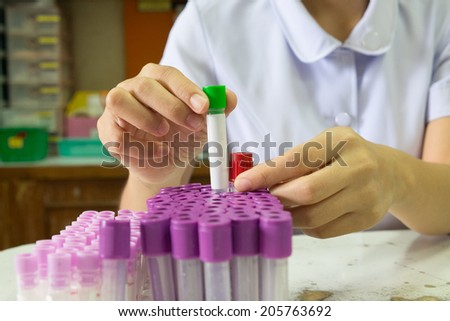 female researcher holding up a test tube and carrying out experiments with different types of blood - stock photo