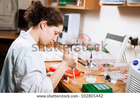 Female researcher in a lab performs sample preparation for DNA electrophoresis making dots of ethidium bromide