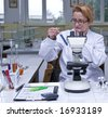 Female researcher looking at a test tube containing a solution, at her workplace in a laboratory.All the inscriptions are mine. - stock photo