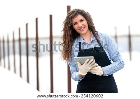 Female researcher technician studying with a tablet and gloves, dressed in office clothes,office shirt and apron in all withe greenhouse. - stock photo