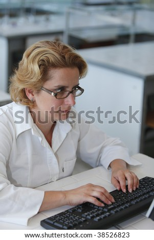 Female researcher typing at her workplace in a laboratory. - stock photo