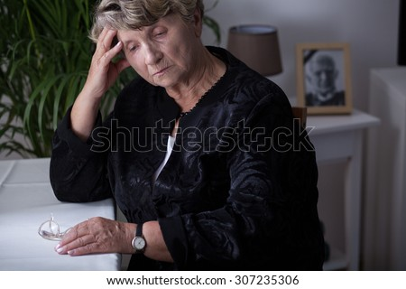 Female retiree being in mourning for dead husband - stock photo