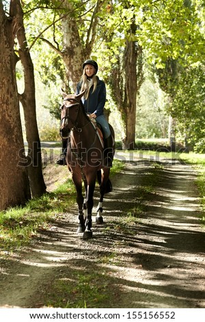 Female rider and horse in the forest. - stock photo