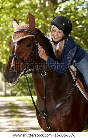 Female rider caressing horse while riding in the woods.