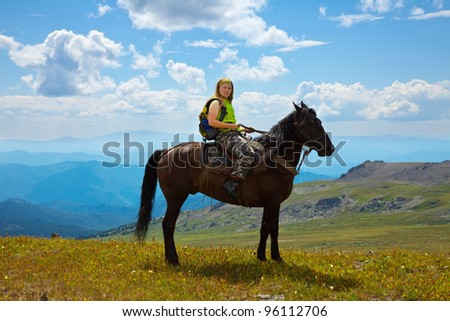 Female rider on horseback at mountains - stock photo