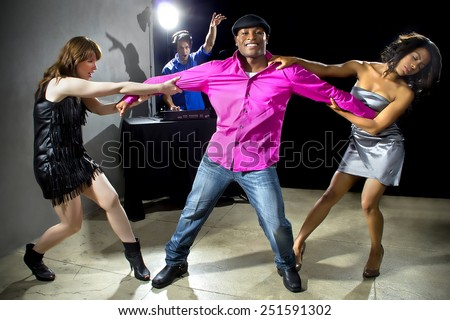 female rivals pulling and grabbing a man in a nightclub - stock photo