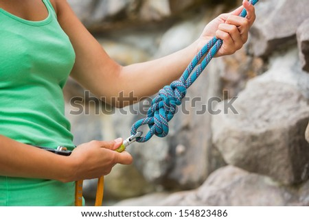 Female rock climber adjusting harness by the rock face - stock photo