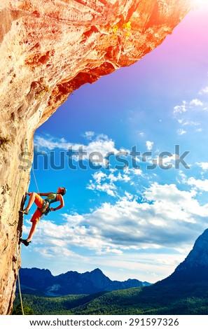 female rock climber climbs on a rocky wall against a blue cloudy sky - stock photo