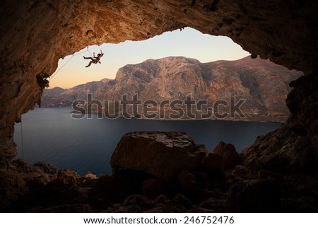 Female rock climber falling of a cliff in a big cave at Kalymnos, Greece  - stock photo