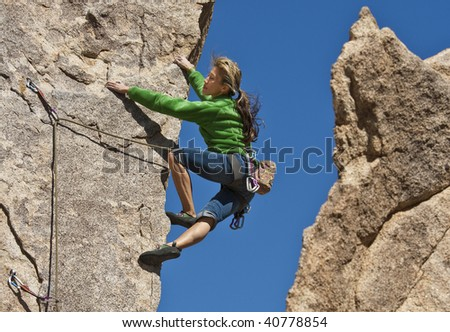 Female rock climber is focused on her next move as she battles her way up a steep cliff in Joshua Tree National Park, California. - stock photo