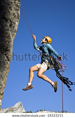 Female rock climber rappelling down a cliff in Yosemite National Park, California, on a sunny, summer afternoon.