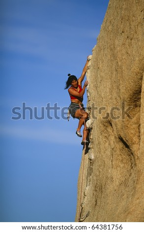 Female rock climber struggles for her next grip on the edge of a steep cliff. - stock photo