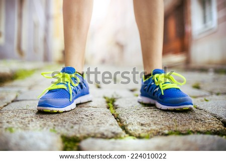 Female runner getting ready for training on tiled pavement in city center, closeup on shoes - stock photo