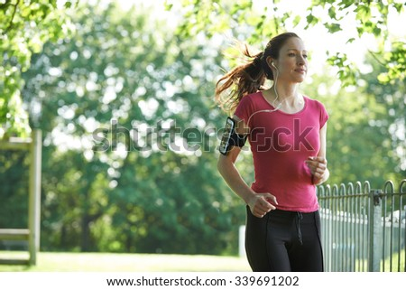 Female Runner In Park With Wearable Technology - stock photo