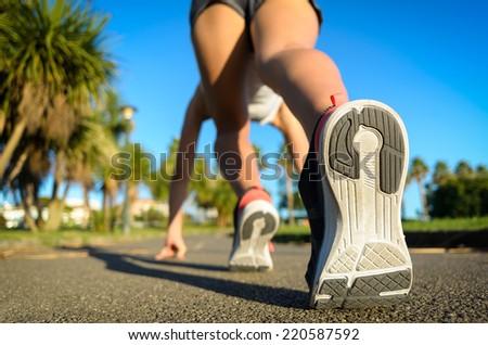 Female runner ready for running sprint. Woman in starting line runner pose for training in a park. - stock photo