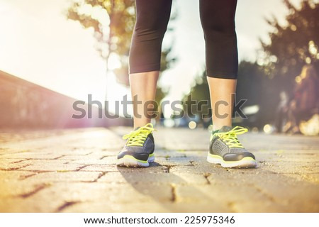 Female runner running on tiled pavement in city quay, closeup on shoes - stock photo