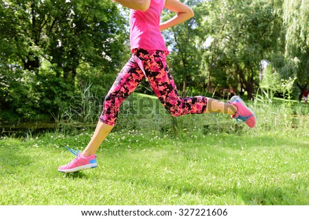 Female runner running shoes and legs in city park. Woman jogging wearing floral capris leggings compression tights and pink running shoes. - stock photo