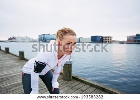 Female runner standing bent over and catching her breath after a running session along river. Young woman taking break after a run. - stock photo
